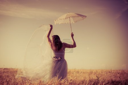 alone in the field: elegant romantic woman in long white dress having fun holding up parasol standing back to camera on blue sky copy space background