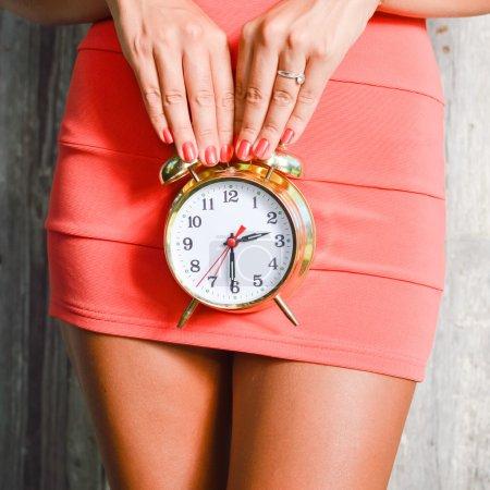 Alarm clock in hands of woman