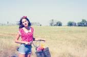 žena na kole s květy v košíku
