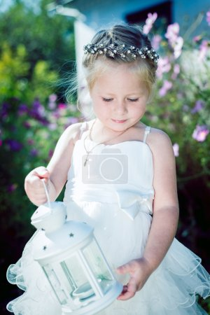 Cute little girl in white lace dress holding candle lantern on green summer outdoor copyspace background
