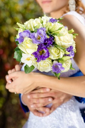 Wedding roses bouquet in bride hands closeup