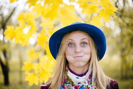 Photo pour Gros plan portrait de sourire heureux élégant blond drôle jolie fille ayant plaisir joyeusement regarder la caméra et souffler les joues sur l'automne copier l'espace en plein air arrière-plan - image libre de droit