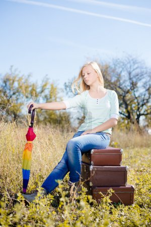 Girl sitting on  retro suitcases