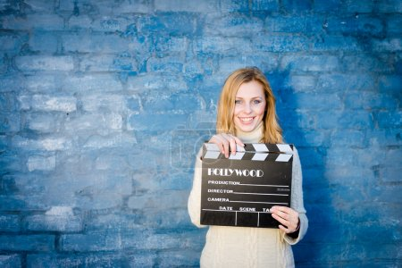 Woman with cinema clapper board