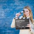 Happy young blond woman in white knitted sweater with cinema clapper board smiling over blue concrete or brick wall copy space background