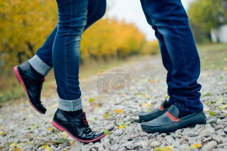 Teenage couple feet closeup in black leather shoes when reaching for kiss