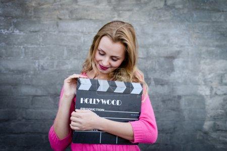 Woman with cinema clapper board