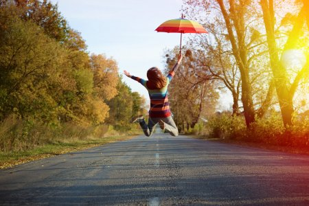 jumping lady on empty road in autumn