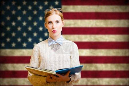 Photo pour Photo de jolie fille dans des verres de gros hipster avec cahiers. Jeune étudiant heureux souriant sur drapeau Usa floue fond. - image libre de droit