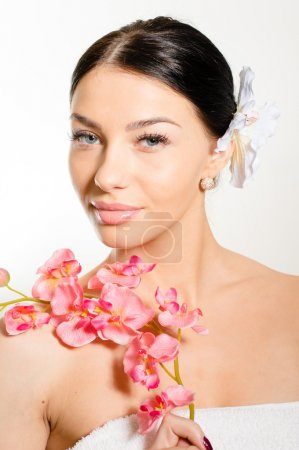 Beautiful woman holding a branch of orchid flowers