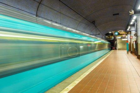 estación de metro con tren de llegada