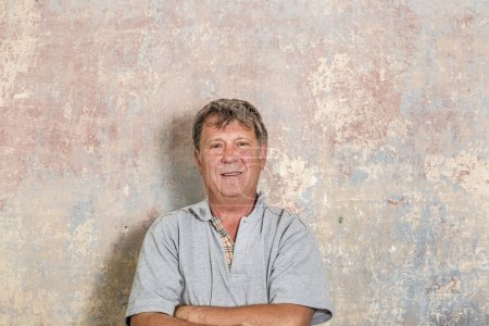 Photo for Portrait of senior man in front of grungy old wall in a rotten house - Royalty Free Image