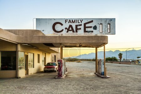 wrecked car at an abandoned petrol station in the desert village