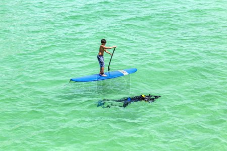 People  enjoy Stand Up Paddle Surfing and diving in the ocean