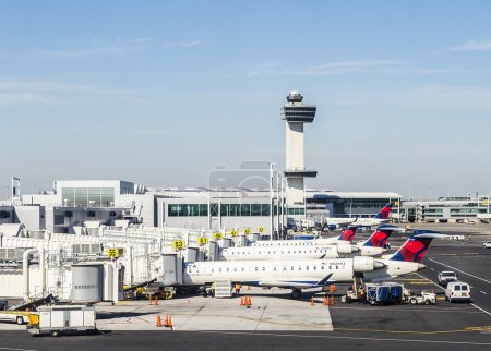 Photo for NEW YORK, USA - OCT 20, 2015: Air Traffic Control Tower and Terminal 4 with Delta Air planes at the gates in JFK Airport in NY. 1963 the airport was rededicated John F. Kennedy International Airport. - Royalty Free Image