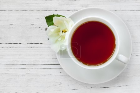Photo for Cup of tea with rose.  Top view, over rustic timber. - Royalty Free Image