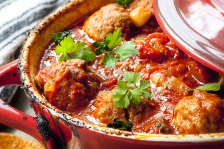 Photo for Chicken meatballs in tomato sauce, cooking in red casserole dish. - Royalty Free Image