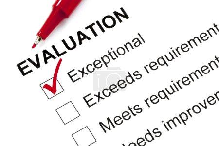 Photo pour Formulaire d'évaluation marquée « exceptionnel » avec stylo rouge. - image libre de droit