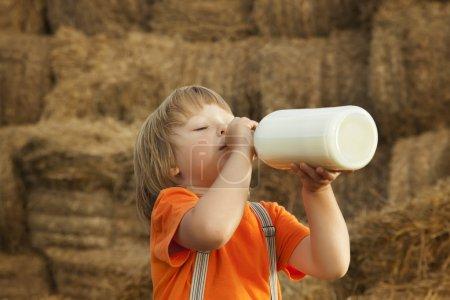 child on a haystack drink milk of bottle