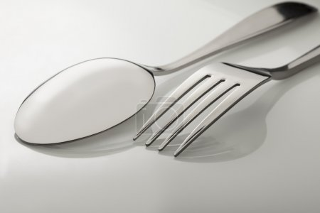Photo for Silverware fork, knife, spoon on white table - Royalty Free Image