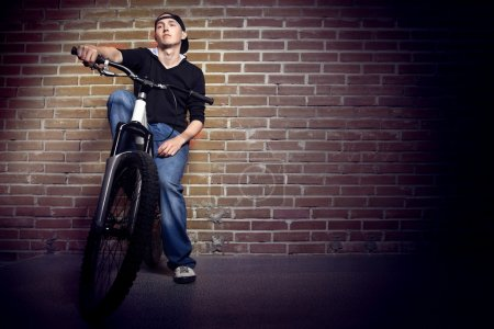 Photo for Teen thinking about life on the background of a brick wall of the city - Royalty Free Image