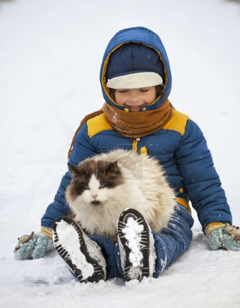 Photo pour Garçon joue avec un chat à l'extérieur en hiver - image libre de droit