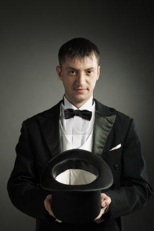Photo pour Magicien tenant chapeau magique, montrant la mise au point, jongle - image libre de droit