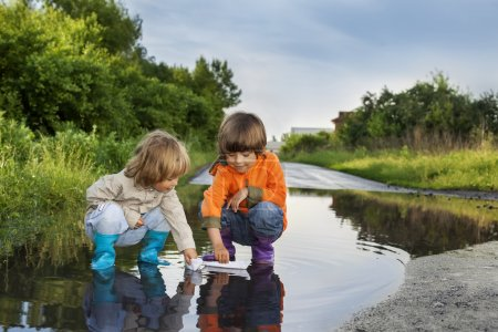 three boy play in puddle