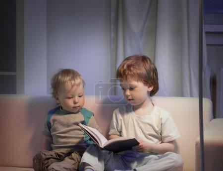 Photo pour Heureux garçons lecture livre à la maison - image libre de droit
