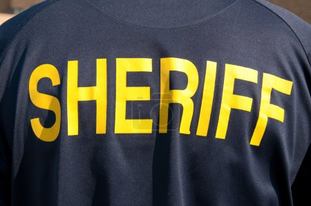 Closeup image of a back of a sheriff's deputy, with text sheriff in yelllow letters