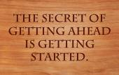 The secret of getting ahead is getting started - motivational quote on wooden red oak background
