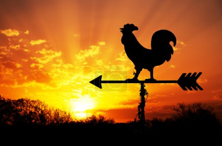 Photo for Rooster weathervane against sunrise with bright colors in clouds, concept for early morning wake up - Royalty Free Image