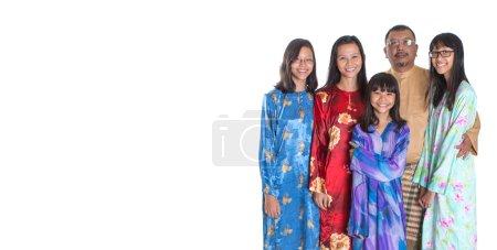 Photo pour Asiatiques parents malais avec des filles adolescentes en tenue traditionnelle sur fond blanc - image libre de droit
