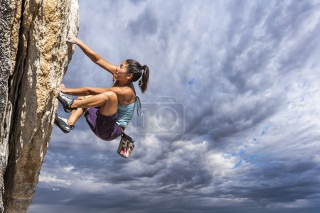 Photo for Female climber dangles from the edge of a challenging cliff. - Royalty Free Image