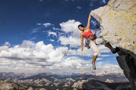 Photo pour Femme grimpeuse pendue au bord d'une falaise difficile . - image libre de droit
