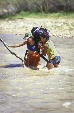 Photo pour Une équipe féminine d'escalade s'équilibre en traversant une rivière . - image libre de droit