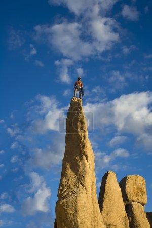 Foto de Escalador celebra en la cumbre de un acantilado desafiante . - Imagen libre de derechos
