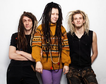 Photo for Three young people, two boys and a girl, with dreadlocks are standing and smiling, white background - Royalty Free Image