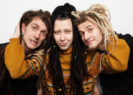 Photo for Cute freaky  girl with dreadlocks and piercings is hugging two boys with dreadlocks and smiling, white background - Royalty Free Image
