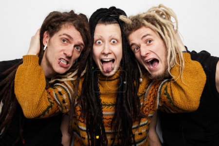 Photo for Collective portrait of three freaky people with dreadlocks and piercings aping, white background - Royalty Free Image
