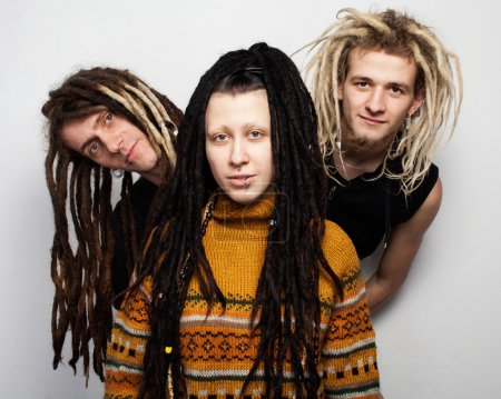 Photo for Group portrait of three young freaks with dreadlocks - two boys are looking out behind the girl in fashionable sweater, white background - Royalty Free Image