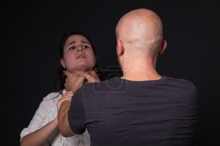 Domestic violence - man is choking woman, black ba...