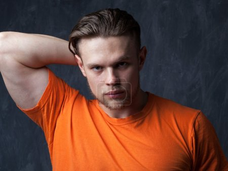 Portrait of a young muscular man in an orange shirt