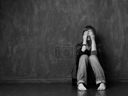 Photo pour Femme désespérée est assise contre le mur, son visage est fermé par ses mains. Noir et blanc - image libre de droit