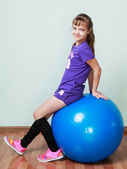 Little girl  is sitting on a blue fit ball at the gym