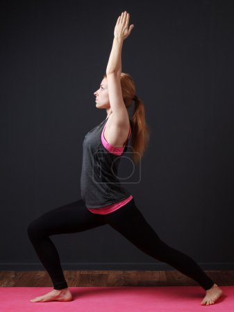 Young blonde woman staying in warrior pose