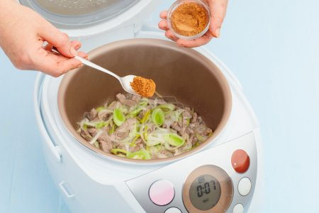 Photo for Cooking chicken with leeks and spices in multicooker closeup - Royalty Free Image