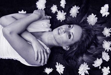 Photo pour Embrassé Dreaming Girl avec de beaux yeux se trouvant sur les fleurs. Portrait noir et blanc. - image libre de droit
