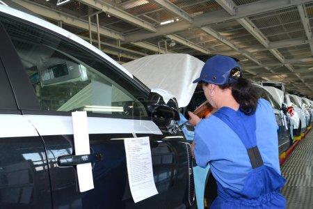 Photo pour Le collecteur femelle fixe un miroir sur une carrosserie de voiture à l'aide du pistolet à vis. Convoyeur d'assemblage de l'usine automobile - image libre de droit