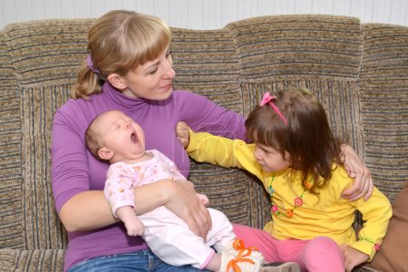 Children's jealousy. The three-year-old girl pushes away mother